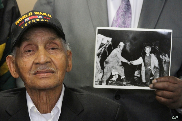 World War II veteran Leonard Larkins at an event in Anchorage, Alaska, celebrating the 75th anniversary of construction of the Alaska Highway while someone holds an iconic photo of a black and white soldier shaking hands when the two sides building t...