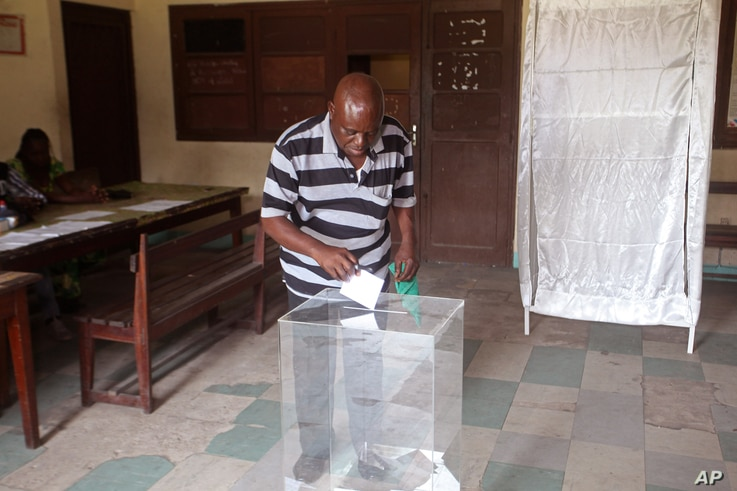 A man cast his ballot at a polling station, in Brazzaville, Congo. Republic of Congo's president, who has ruled the Central African country for more than 30 years, March 20, 2016.
