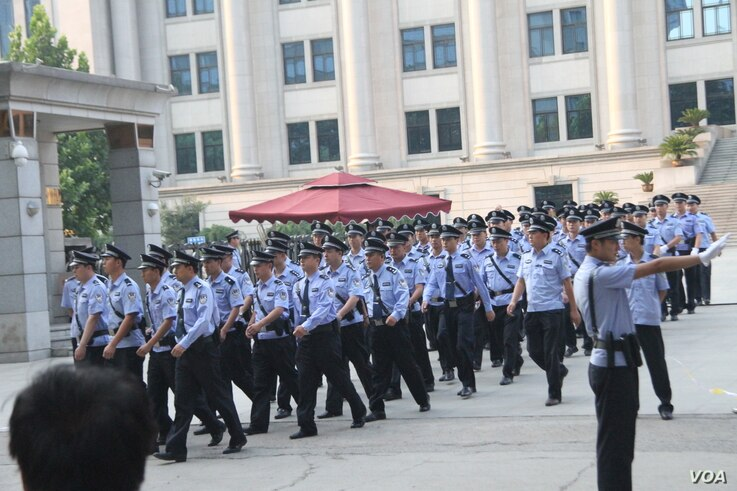 Chinese police officers march out of the Jinan Intermediate People's Court in Jinan in eastern China's Shandong province, August 21, 2013. (Wang Fei for VOA)