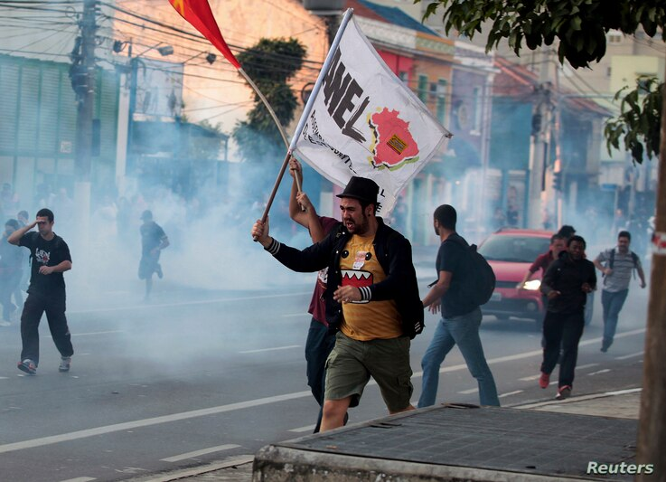 Demonstrators run from tear gas fired by police outside Ana Rosa subway station during the fifth day of metro workers' strike in Sao Paulo, Brazil, June 9, 2014.