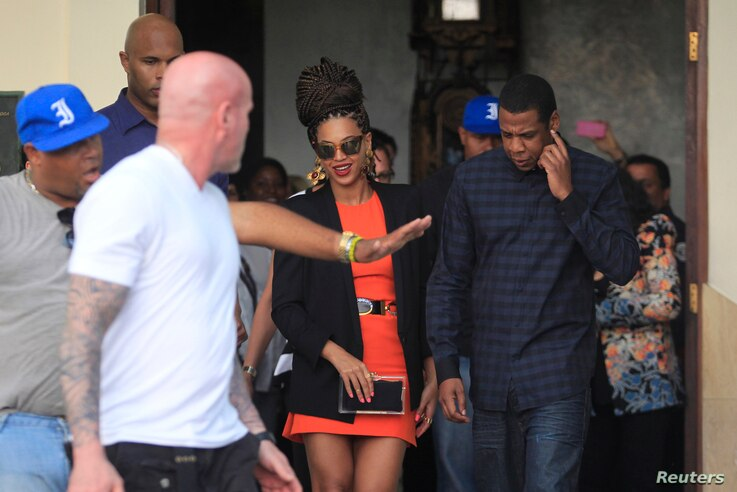 U.S. singer Beyonce (C) and her husband rapper Jay-Z (R), are escorted by bodyguards as they leave their hotel in Havana, April 4, 2013.