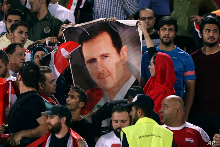 FILE - Syrian soccer fans hold a poster of their president, Bashar al-Assad, before a match with Iran, at Azadi Stadium in Tehran, Iran, Sept. 5, 2017.