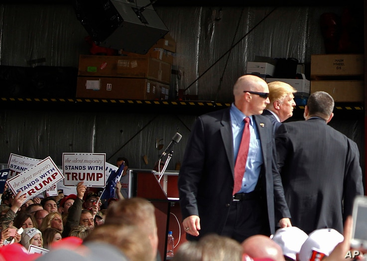 FILE - Secret Service agents guard Republican presidential candidate Donald Trump after a man rushed the stage during a campaign rally at the Wright Brothers Aero Hangar at Dayton International Airport in Vandalia, Ohio, March 12, 2016.