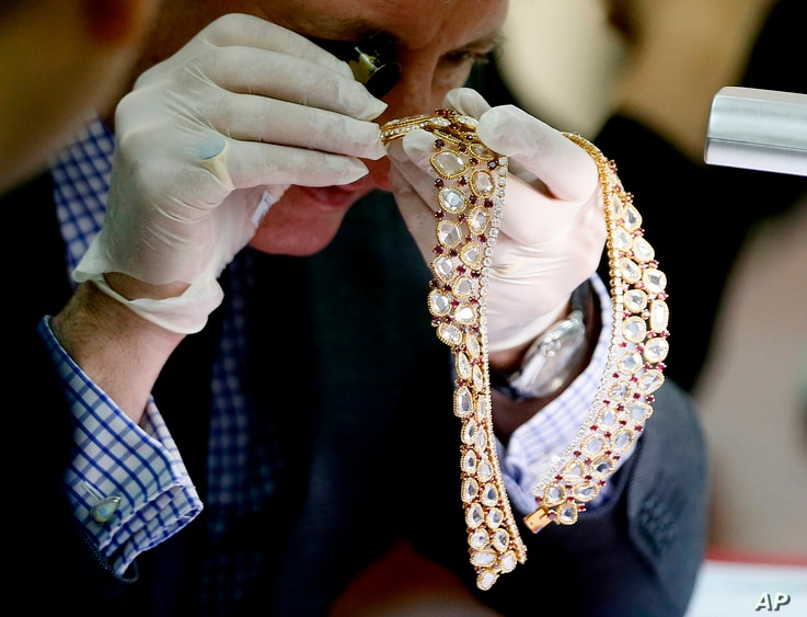 Christie's auction house appraiser David Warren examines a set of jewelry from Roumeliotes Collection, one of three sets of the Marcos Jewelry Collection, during appraisal at the Central Bank of the Philippines, Nov. 24, 2015 in Manila, Philippines. ...