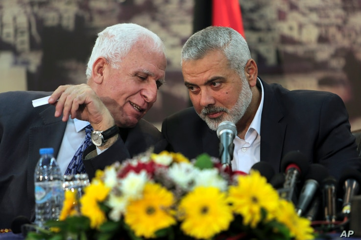 Senior Fatah official Azzam al-Ahmad, left, talks to Gaza's Hamas Prime Minister Ismail Haniyeh, during a press conference at Haniyeh's residence in Shati Refugee Camp, Gaza Strip, Wednesday, April 23, 2014.