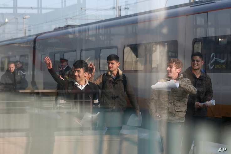 One Syrian and five Afghan boys wave on the platform of the Calais train station, northern France, as they leave for Britain, Oct. 13, 2016.