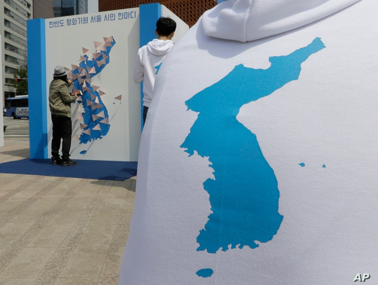 A woman puts a sign bearing messages wishing for peace in the two Koreas on a map of the Korean Peninsula in Seoul, South Korea, April 26, 2018.