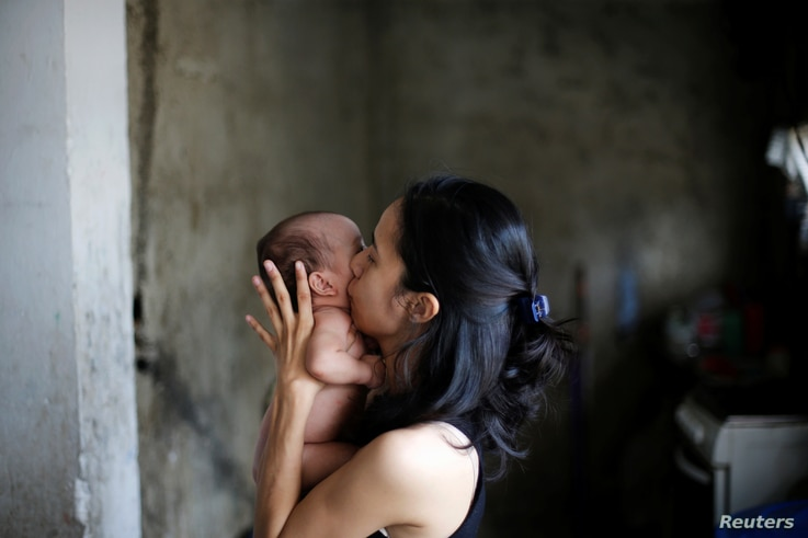 Yennifer Padron kisses her baby in her house at Petare slum in Caracas, Venezuela, Aug. 21, 2017.