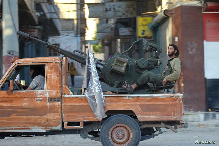 Members of al Qaeda's Nusra Front ride on a pick-up truck mounted with an anti-aircraft weapon in the town of the northwestern city of Ariha, after a coalition of insurgent groups seized the area in Idlib province, May 29, 2015.