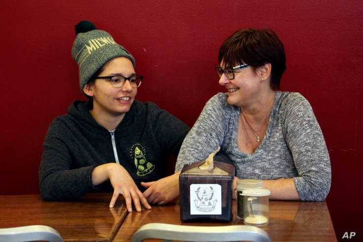 Andrea Ledesma (left) talks with her mother, Cheryl Romanowski, at Classic Slice pizza restaurant, where Ledesma works, in Milwaukee. Ledesma, 28, says her parents owned a house and were raising kids by her age. Not so for her, even though she has a ...