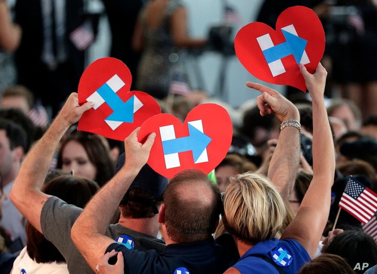 Supporters for Democratic presidential candidate Hillary Clinton hold up campaign logos during a presidential primary election night rally in New York, June 7, 2016..