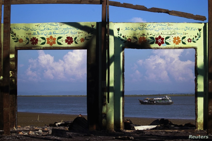 A boat is framed by the ruins of a destroyed mosque in a part of Pauktaw township that was burned in recent violence in Rakhine state, Burma, October 27, 2012.