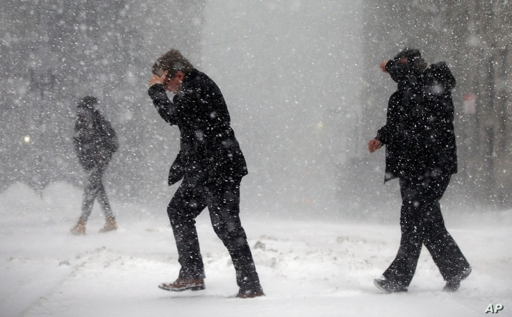 Pedestrians cross the street in downtown Boston, Jan. 4, 2018. A massive winter storm swept from the Carolinas to Maine on Thursday, dumping snow along the coast and bringing strong winds that will usher in possible record-breaking cold.