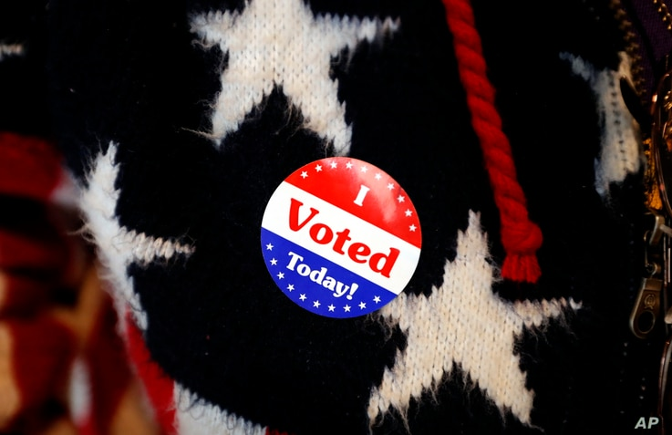Maria Morahn, of Osceola, Iowa, wears a sticker after casting her ballot in the general election, Nov. 6, 2018, at the United Methodist Church in Osceola, Iowa.