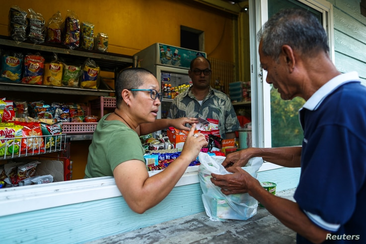 Boodsabann Chanthawong works with her husband at her stall near her house, days after she ended her novice monkhood, at the Songdhammakalyani monastery, in Bangkok, Thailand, Dec. 16, 2018. A growing number of women defy generations of Thai Buddhist ...