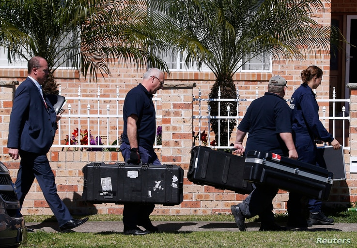 Members of the Australian Federal Police (AFP) forensic unit carry equipment into a house that was involved in pre-dawn raids in the western Sydney suburb of Guilford September 18, 2014.