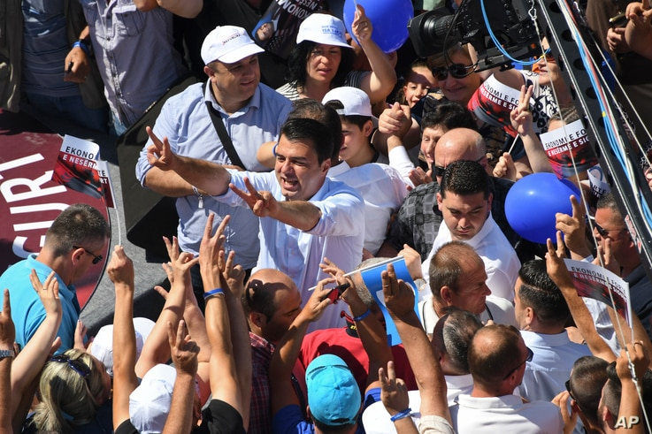 In this photo taken June 20, 2017, Lulzim Basha, leader of the Democratic Party (PD), flashes victory sign at his supporters at an electoral rally in the town of Kavaja, Albania.