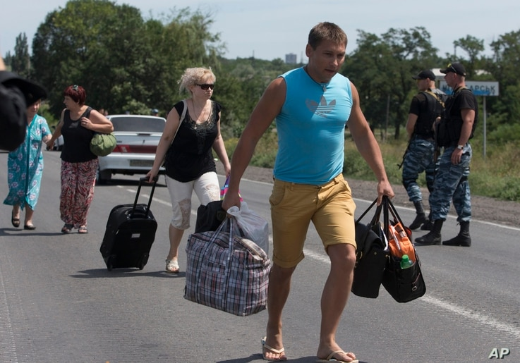 Self-proclamed Donetsk People's Republic policemen watch refugees fleeing  Shakhtarsk, Donetsk region, eastern Ukraine on Monday, July 28, 2014. An international police team abandoned its attempt to reach the crash site of a Malaysia Airlines plane f...