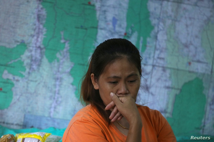 A relative of the 12 boys and their soccer coach trapped in the Tham Luang cave complex listens to a news conference about the death of a Thai rescue diver after he fell unconscious during part of an operation, near the cave complex in the northern p...