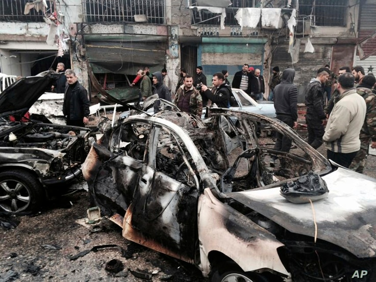 In this photo released by the Syrian official news agency SANA, Syrian citizens and security forces gather next to damaged cars at the scene where explosion hit a commercial street, in the costal town of Jableh, Syria, Jan. 5, 2017.