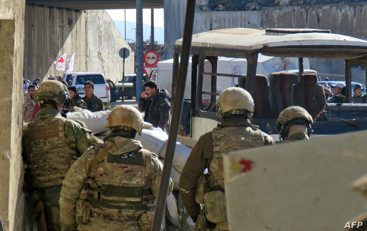 Russian soldiers gather in the government held side of the embattled city of Aleppo before the start on an evacuation operation of rebel fighters and their families from rebel-held areas on Dec. 15, 2016.