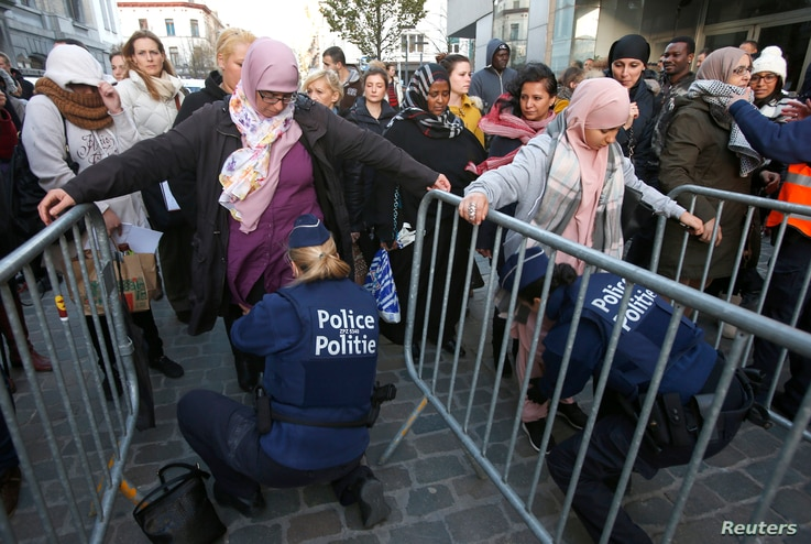 Residents of the Brussels suburb of Molenbeek are searched by police vefore taking part in a memorial gathering to honor the victims of the recent deadly Paris attacks, in Brussels, Belgium, Nov. 18, 2015.