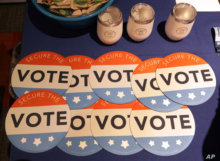 FILE - Computer mouse pads with Secure the Vote logo on them are seen on a vendor's table at a convention of state secretaries of state in Philadelphia, July 14, 2018.