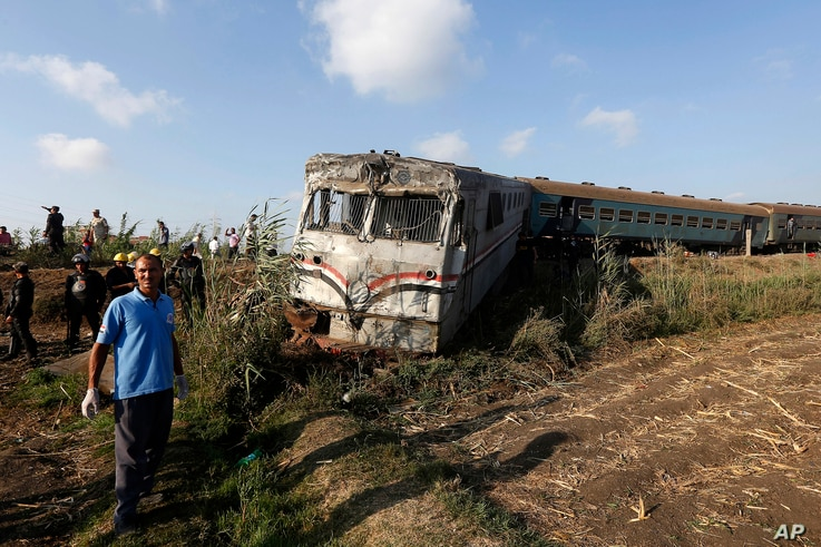 Onlookers gather at the scene of a train collision just outside Egypt's Mediterranean port city of Alexandria, Aug. 11, 2017.