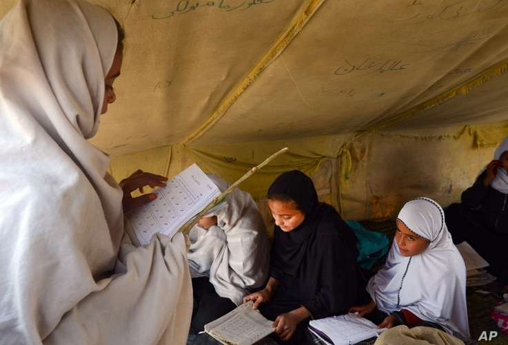 FILE - Afghan students attend class in a tent in Jalalabad, capital of Nangarhar province, Afghanistan, Dec. 16, 2015. Analysts say by targeting students and education centers, militants are aiming at the heart of the society.