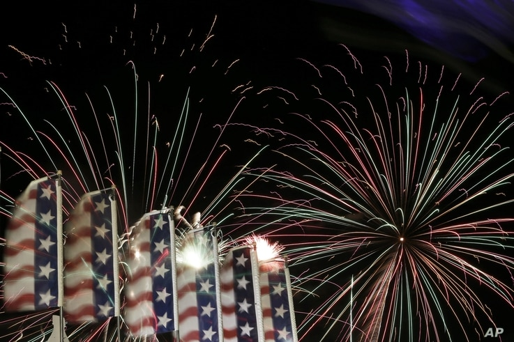 Banners with the United States flag colors wave as fireworks burst in the air during the Fourth of July Independence Day show at State Fair Meadowlands, in East Rutherford, N.J., July 3, 2012.