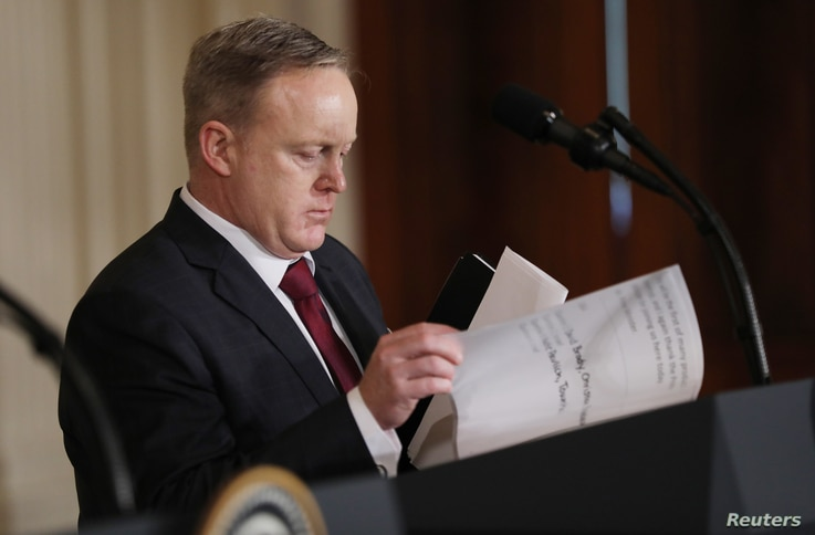 White House Press Secretary Sean Spicer goes through papers on the podium for  President Donald Trump before a joint news conference with Israeli Prime Minister Benjamin Netanyahu.