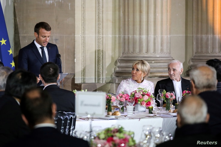French President's wife Brigitte Macron and French singer Charles Aznavour listen to speeches at the start of an official state dinner with with Japan's Crown Prince Naruhito at the Chateau de Versailles castle, near Paris, France, Sept. 12, 2018.