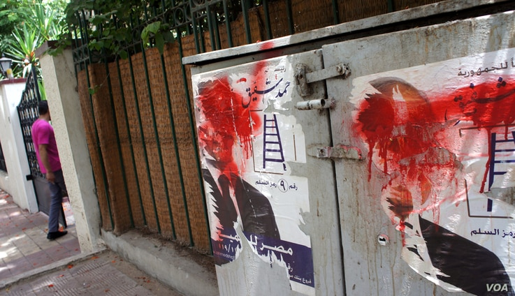 Posters of Eygptian presidential candidate Ahmed Shafiq defaced outside his Cairo headquarters, May 29, 2012. (E. Arrott/VOA)