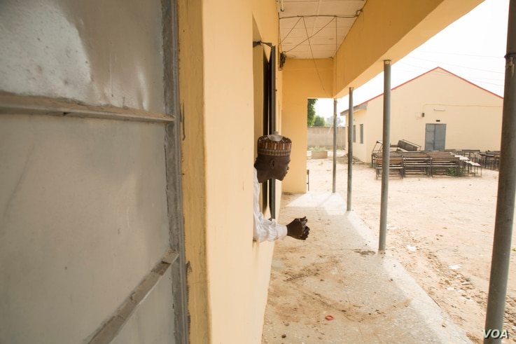 Baba Goni Ibrahim, a science teacher at an all-girls high school in Maiduguri, Nigeria, looks out of a classroom window at the campus, Oct. 5, 2016. (C. Oduah/VOA)
