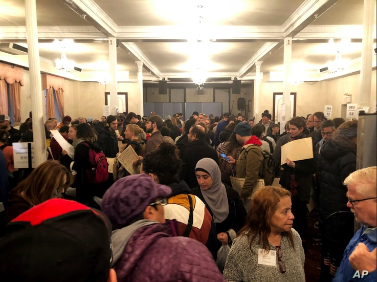 People stand in numerous lines as they wait to vote at Kingsboro Temple Seventh-day Adventist Church in the Brooklyn borough of New York, Nov. 6, 2018. The malfunctioning equipment turned a polling place in Brooklyn's Park Slope neighborhood into a...