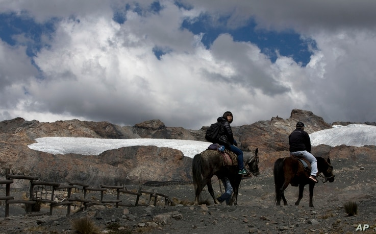 """A group of tourists ride horses to the Pastoruri glacier in a tour called """"The Route of Climate Change"""" in Huaraz, Peru, Aug. 12, 2016."""
