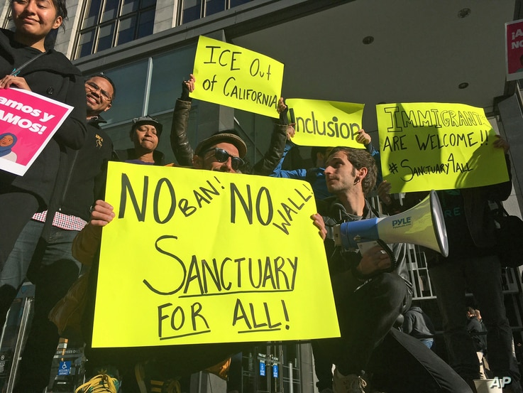 FILE - Protesters hold up signs outside a courthouse where a federal judge hears arguments in a lawsuit challenging President Donald Trump's executive order to withhold funding from communities that limit cooperation with immigration authorities, in