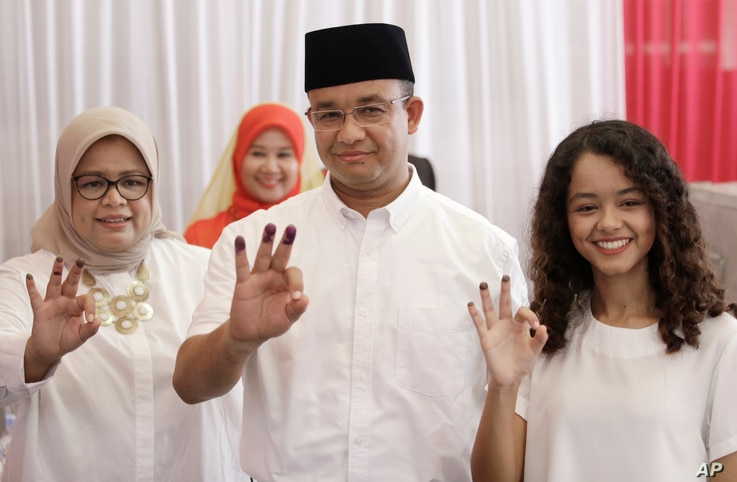 Gubernatorial candidate Anies Baswedan, center, and his family show their ink-dipped fingers after giving their votes during the local election in Jakarta, Indonesia, April 19, 2017.