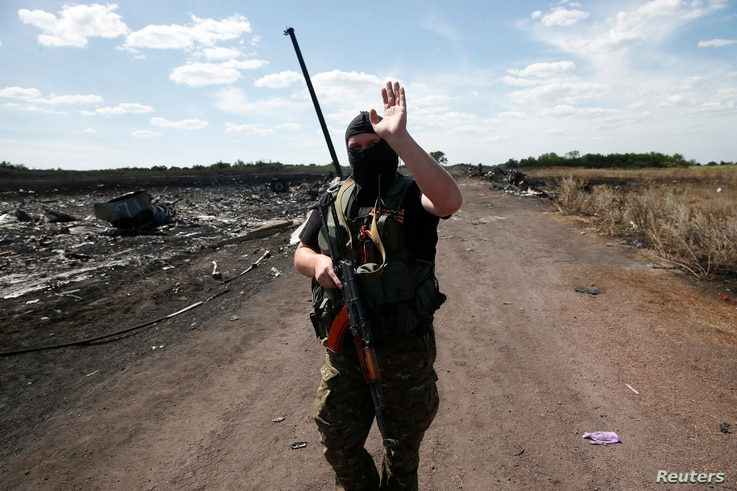 An armed pro-Russian separatist gestures to reporters at the crash site of Malaysia Airlines Flight MH17, near the village of Grabovo, Donetsk region, Crimea, July 21, 2014.