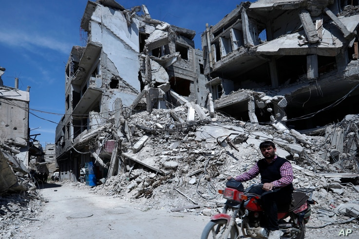 A man rides past destruction in the town of Douma, the site of a suspected chemical weapons attack, near Damascus, Syria, April 16, 2018.