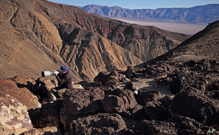 FILE - Jason O. Watson looks through a telephoto lens on a cliff overlooking the nicknamed Star Wars Canyon in Death Valley National Park, California, Feb. 28, 2017.