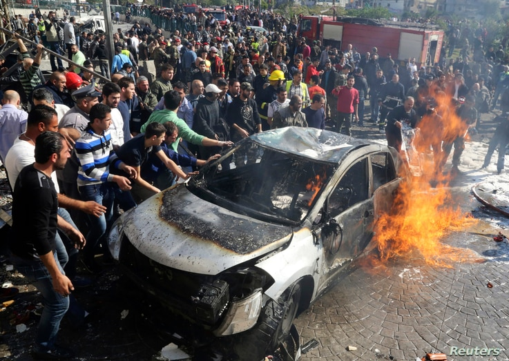 Civil defence members and civilians put out a fire at the site of an explosion in the southern suburbs of Beirut, Feb. 19, 2014.