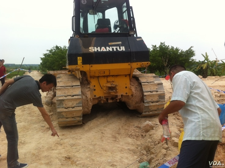 Men point to where a bulldozer killed a young girl in Fujian province, China, August 28, 2013. (QQ)