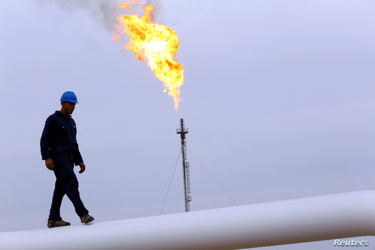 A worker walks on an oil pipeline at Khurmala oilfield on the outskirts of the city of Arbil, in Iraq's Kurdistan region December 4, 2013. REUTERS/Stringer (IRAQ - Tags: POLITICS ENERGY) - RTX163IY