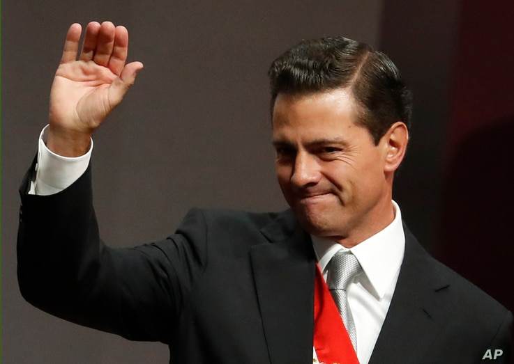 Mexican President Enrique Pena Nieto waves to supporters after delivering his sixth and final State of the Nation address at the National Palace in Mexico City, Sept. 3, 2018. President-elect and longtime opposition leader Andres Manuel Lopez Obrador...