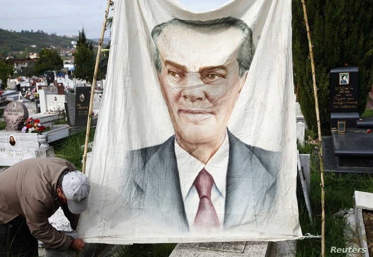 An Albanian communist hangs a banner showing the late communist dictator Enver Hoxha in the public cemetery in Tirana, April 11, 2012.