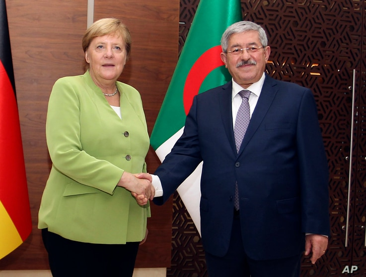 German Chancellor Angela Merkel shakes hands with Algerian Prime Minister Ahmed Ouyahia ahead of talks in Algiers,  Sept.17, 2018.