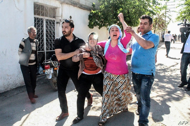 FILE - Residents flee as rockets fired from Syria land in the Turkish town of Kilis, April 19, 2016.
