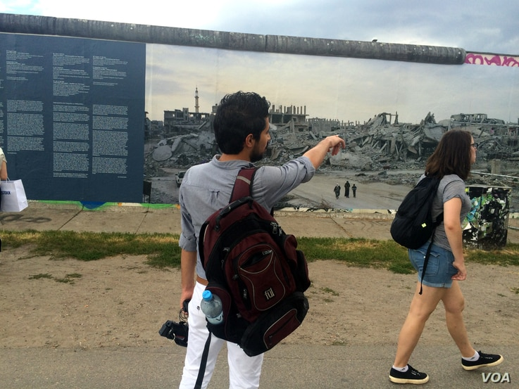 A Syrian refugee at the Berlin Wall looks at a photo gallery of the destruction of his country by war, June 30, 2016. Young Syrian men say they want to go home, but only after the war. (H. Murdock/VOA)