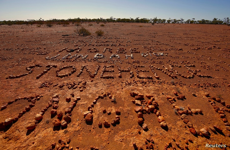 """Stones arranged by tourists lie on the ground, spelling out their names and the places they are from, in the area known as """"The Address Book,"""" located on the outskirts of the outback town of Stonehenge in Queensland, Australia, Aug. 12, 2017."""